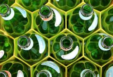A collection of green glass bottles vertically arranged in a yellow container.